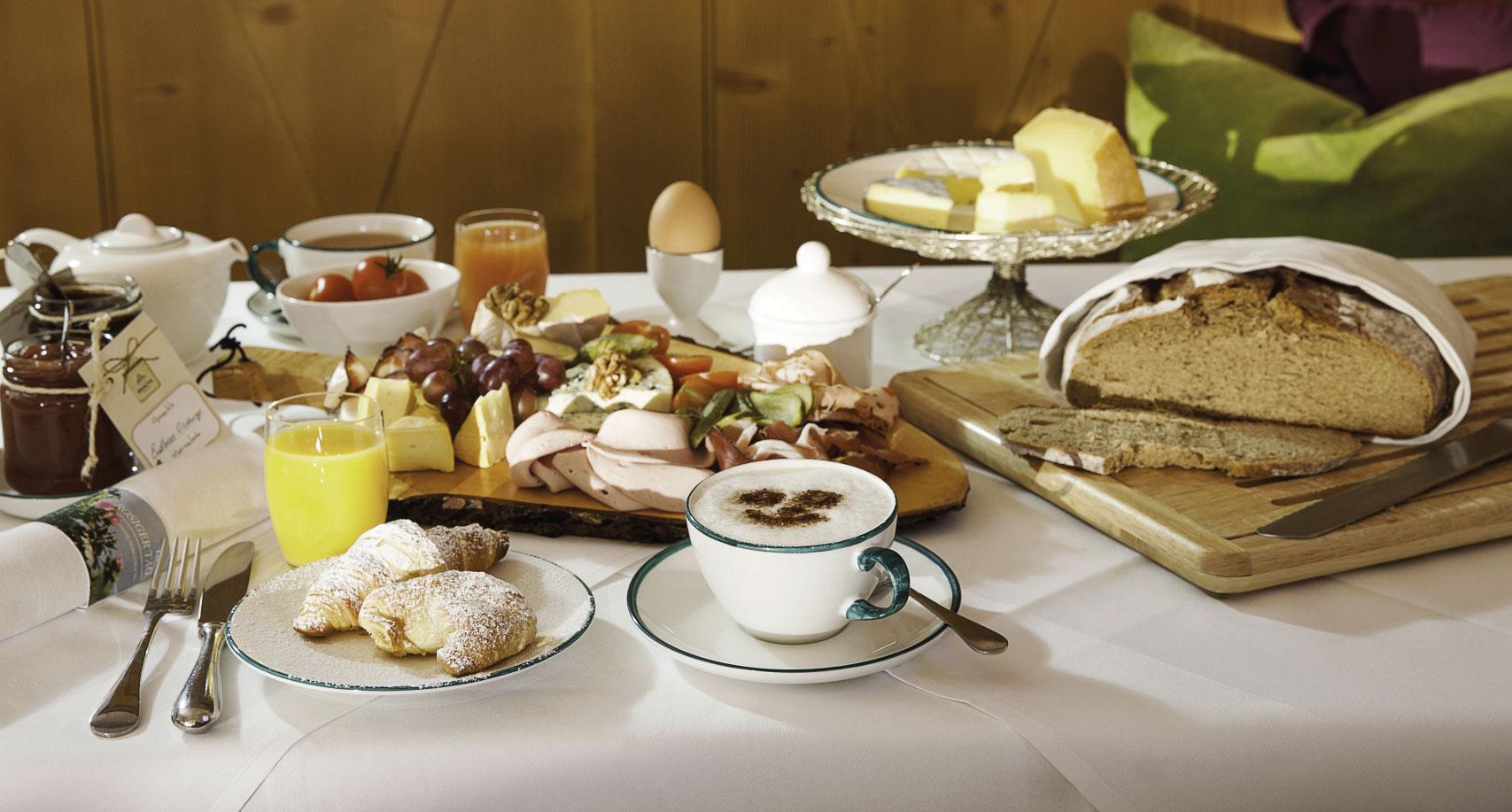Frühstück mit Croissant, Kaffee, Brot und Obst