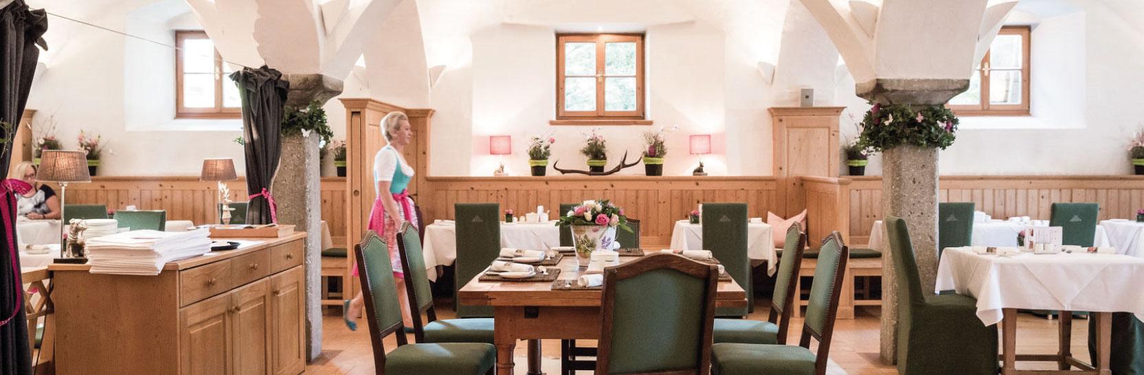 Frau geht im Dirndl durch Speisesaal