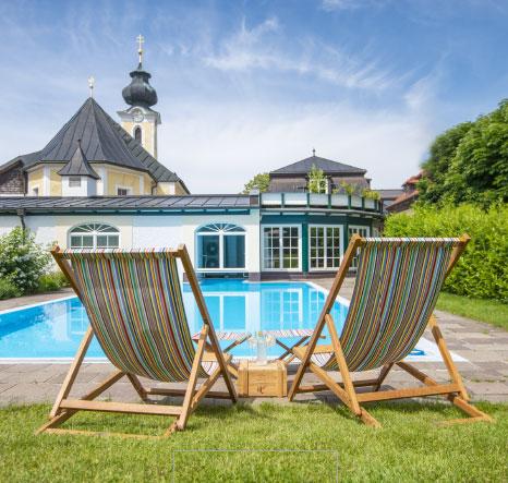 Zwei Liegestühle vor einem Pool im Freien