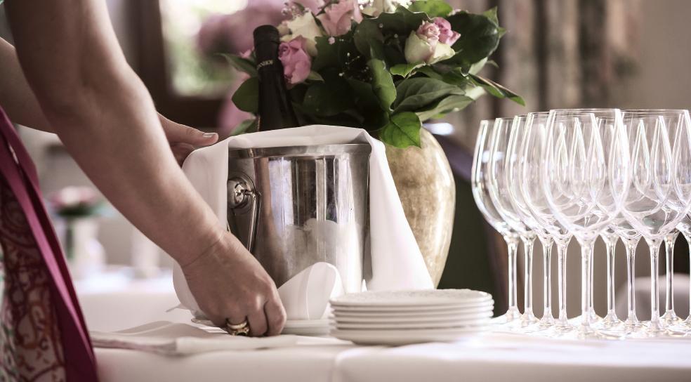 Kellnerin deckt den Tisch