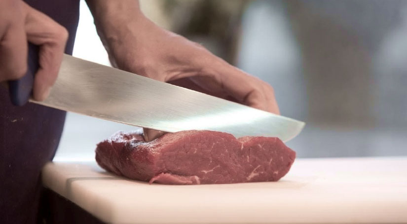 Fleisch wird mit Messer geschnitten