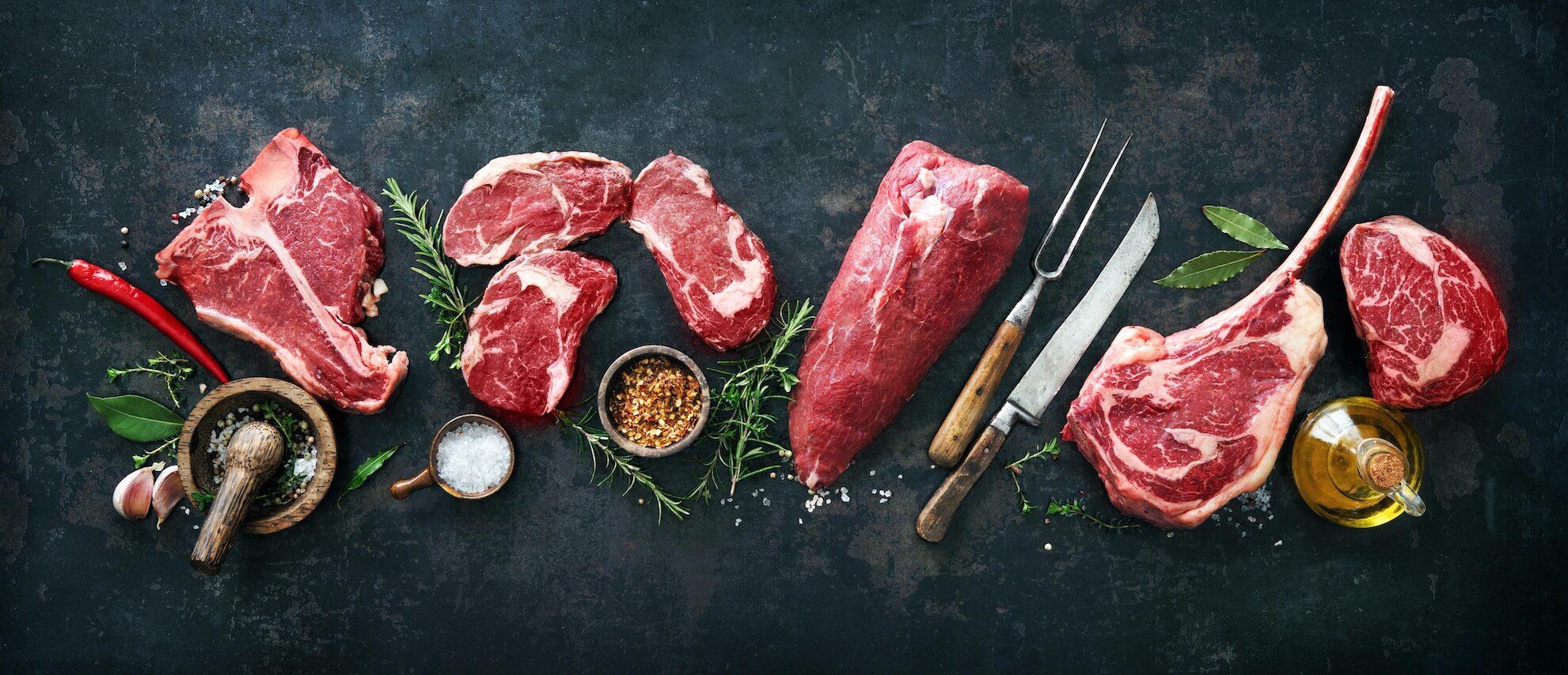 verschiedene rohe Fleischstücke auf einem schwarzen Hintergrund