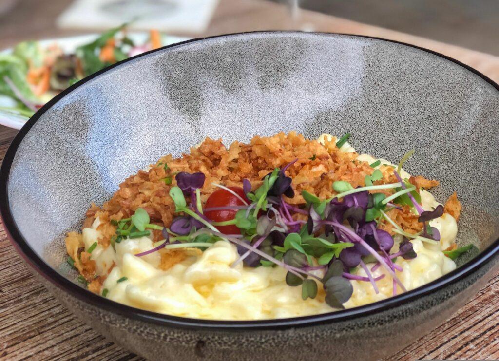 Käsespetzle mit Zwiebel und Salat in einem Teller