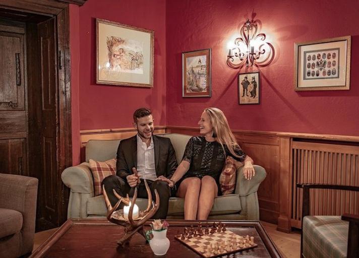 Zwei Personen lachend auf einer Couch vor einer roten Wand