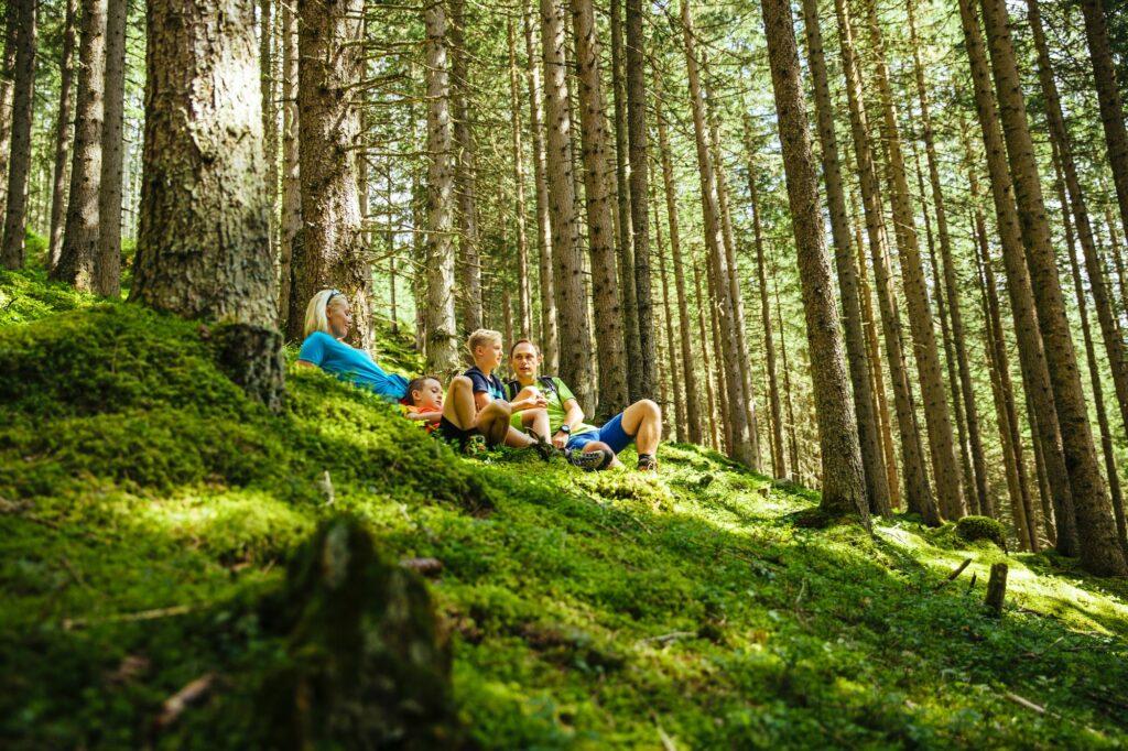 Zwei Erwachsene und zwei Kinder machen eine Pause beim Wandern