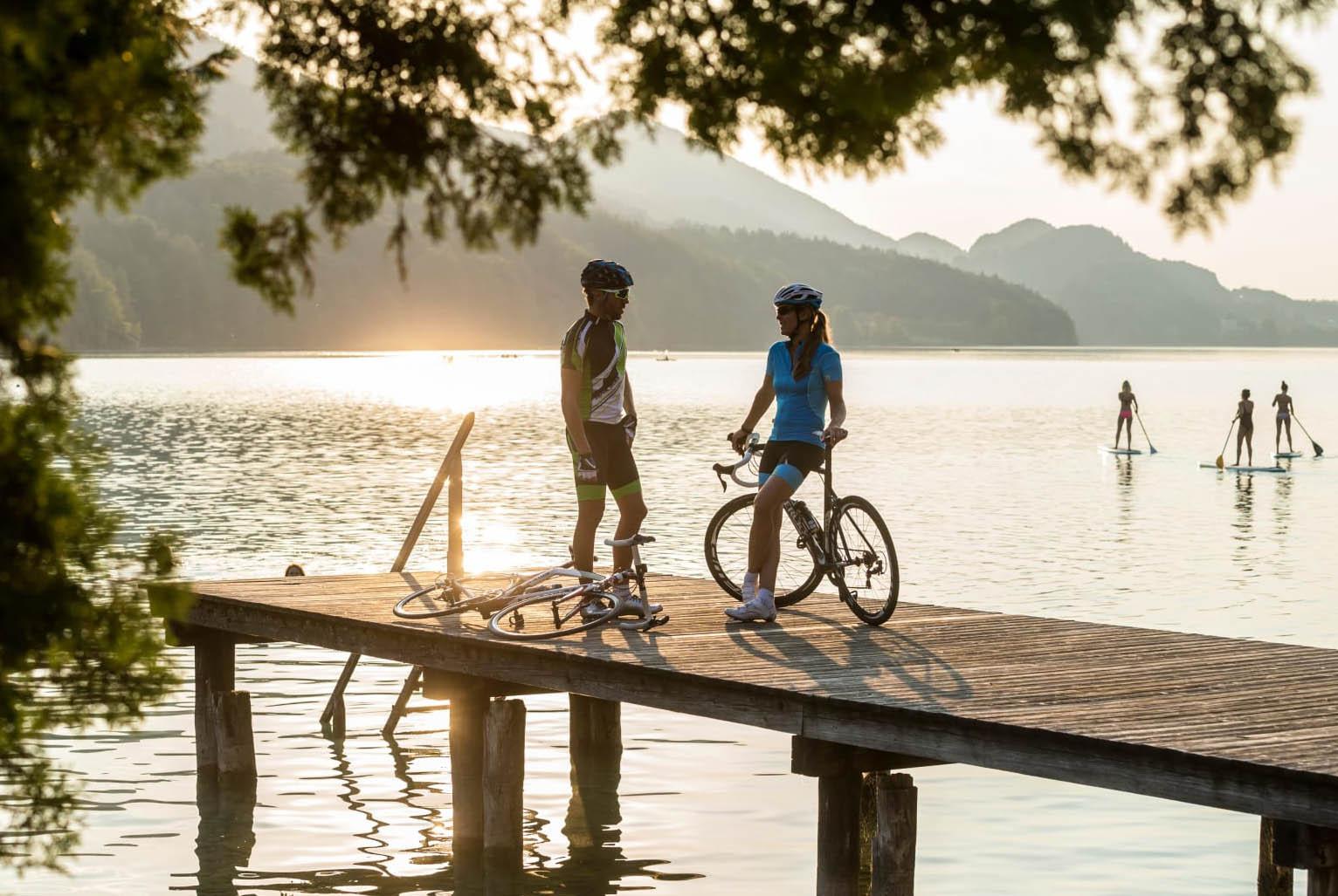 Mann und Frau auf Steg vor See, drei Personen im Hintergrund
